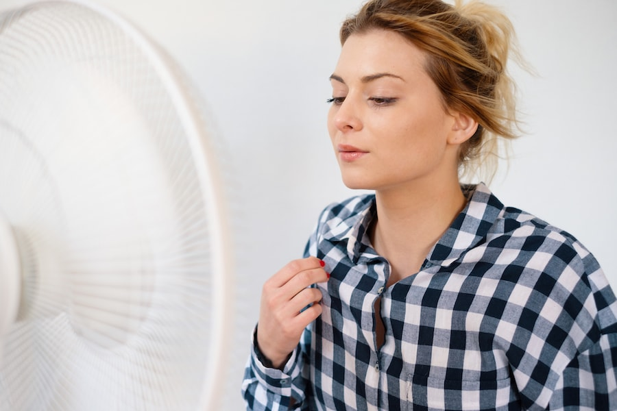 Girl face expression cooling in front of a fan.