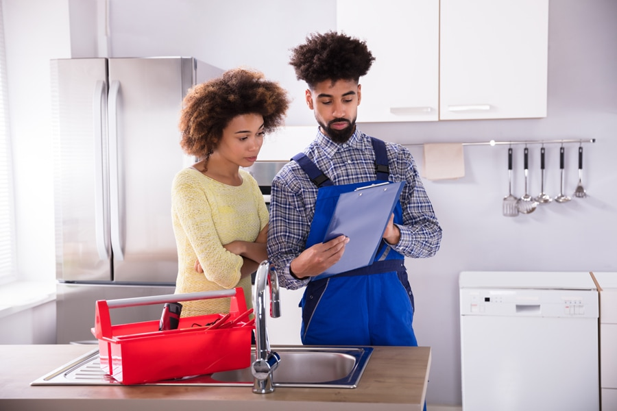 Young Male Plumber Looking At Woman Signing Invoice In Kitchen.