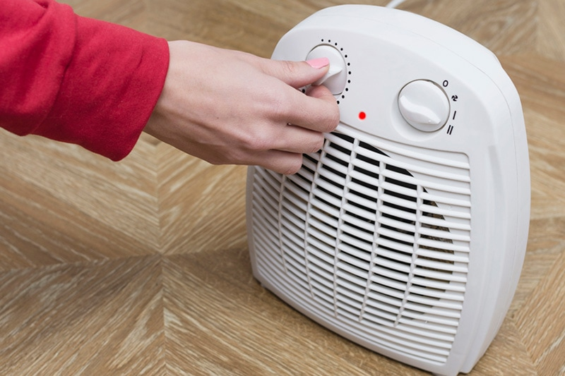 how can I save money on my heating bill this winter?, female hand adjusting space heater