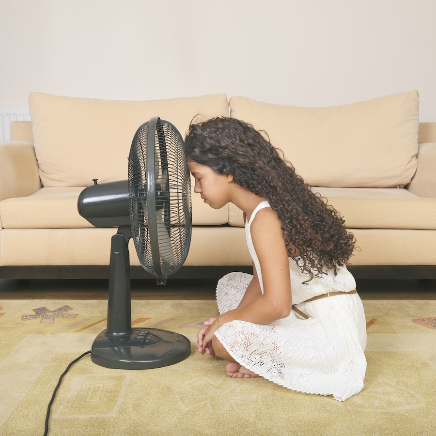 Small child in front of fan.