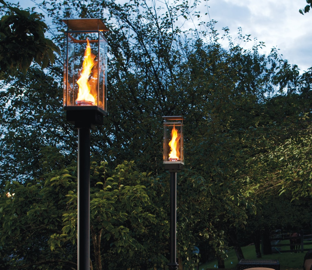 Lit outdoor torches in frot of beautiful trees later in the evening.