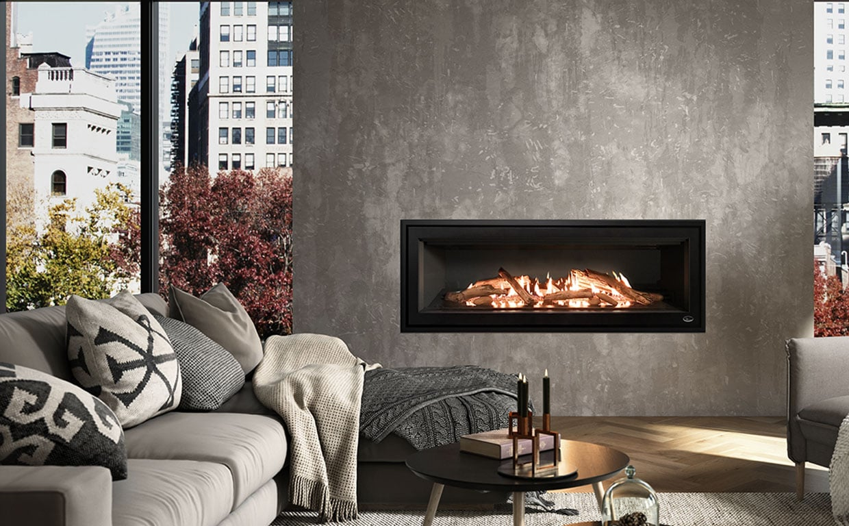 Large Fireplace set inside dark, concrete colored wall.