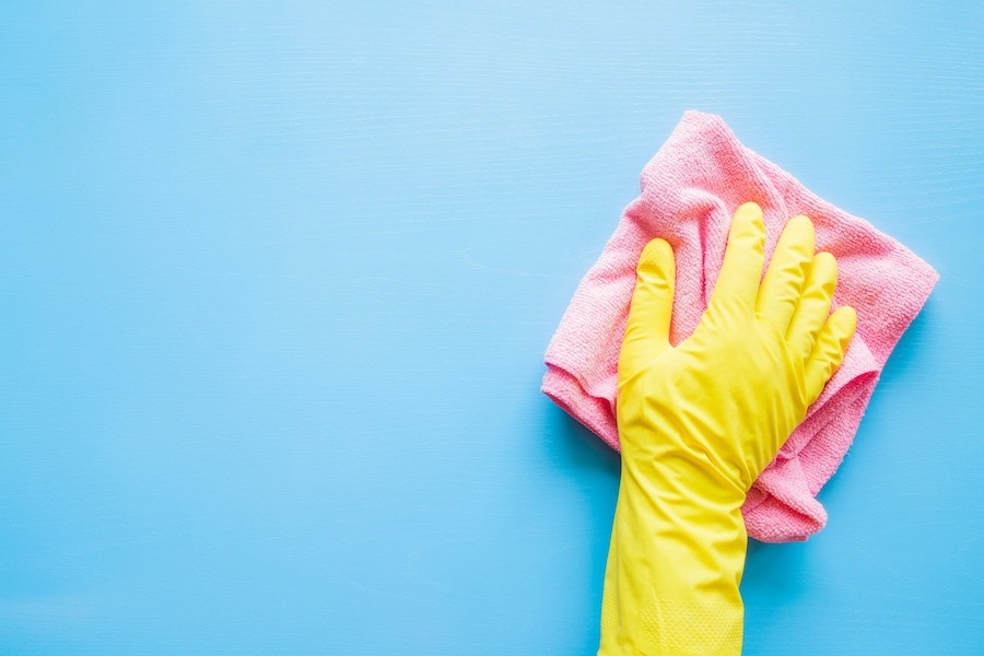 Yellow glove cleaning blue wall.